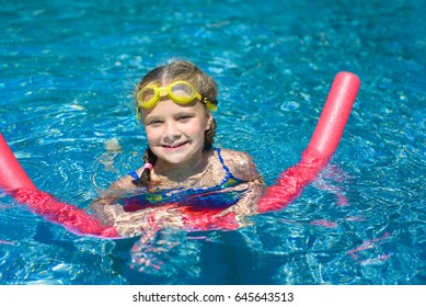 Happy little girl swimming with a pink foam noodle in a pool