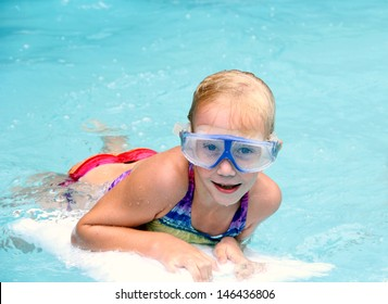 Happy little girl swimming in the pool with diving mask