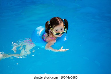 happy little girl swims in the pool in summer in sunglasses, space for text
