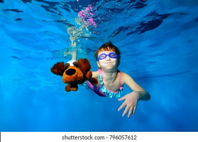Happy little girl swims underwater in the pool, holding a toy dog in hand, looking at camera and smiling. Portrait. Horizontal orientation. The view from under the water