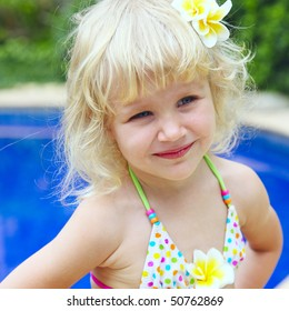 happy little girl in a swimsuit at the pool