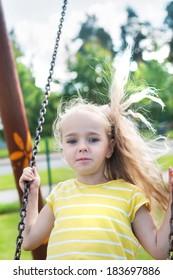 Happy little girl swinging on a swing