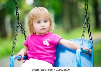 Happy little girl swinging on playground area