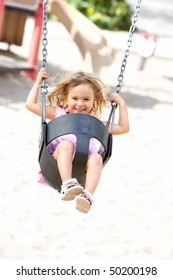 Happy  little girl swinging in the park