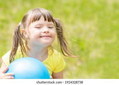Happy kleines Mädchen mit Syndrom Down hält Ball in einem Sommerpark. Leerzeichen für Text