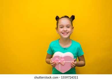 happy little girl with tails standing isolated over yellow background holding shopping pink bag. smiles thoughtfully.