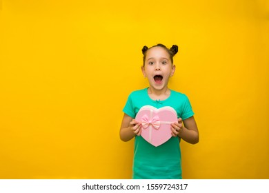 happy little girl with tails standing isolated over yellow background holding shopping pink bag in surprise.