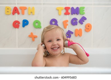 Happy little girl taking a bath and playing with tea infusers as a headphones . Beautiful wide smile of little girl with great healthy white teeth. Water fun for kids.