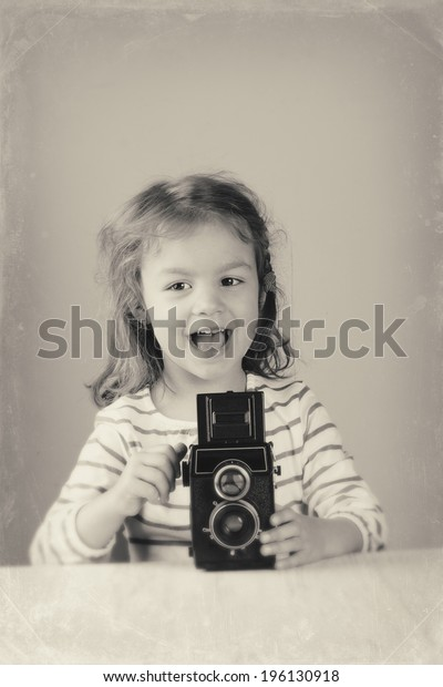Happy little girl taking pictures with a vintage film lomography camera. Made in USSR. Black and White photography.