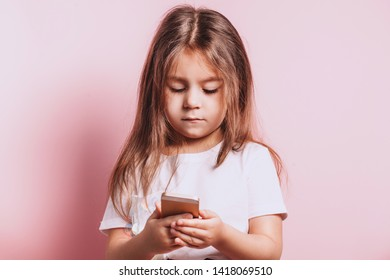 Happy little girl talking on telephone on pink background