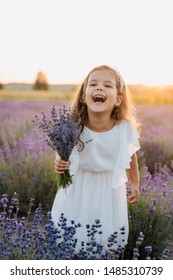 Happy Little Girl with Violet Lavender Bouquet. Joyful Fun Kid Holding Bunch of Flowers. Caucasian Child Model Laughing at Camera. Blooming Meadow, Countryside Landscape Bokeh Background