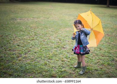 Happy little girl walking with an umbrella