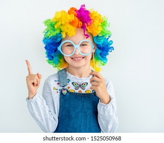 Happy little girl wearing clown wig with raised pointing finger