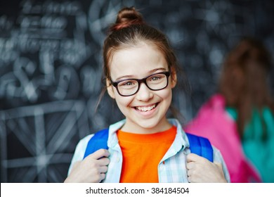 Happy little girl wearing glasses looking at camera