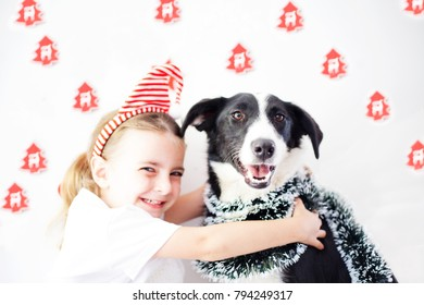 Happy Little girl wearing a headband and dog at Christmas