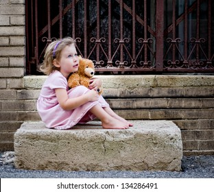 Happy little girl wearing pink dress sitting on concrete step holding teddy bear and looking up
