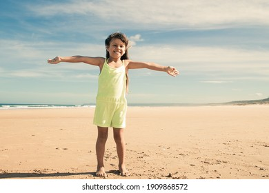Happy little girl wearing summer cloth, standing with open arms on golden sand, looking at camera, spending leisure time on beach at sea. Full length, front view. Childhood concept