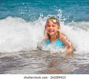 Happy little girl wearing swim goggles playing in the sea