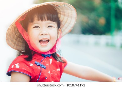 Happy little girl wearing Vietnamese hat in red Ao dai Vietnam Traditional dress or chinese Traditional dress and ride bicycle at park outdoor.Dress culture Vietnamese concept.Happy chinese new year.