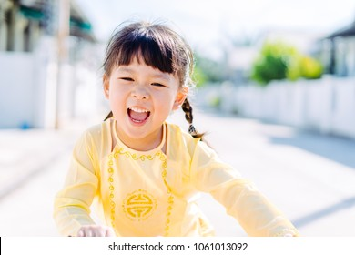 Happy little girl wearing Vietnamese hat in yellow Ao dai Vietnam Traditional dress and ride bicycle at park outdoor.Dress culture Vietnam concept.
