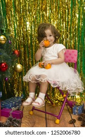 happy little girl in white dress sit on chair  christmas tinsel background