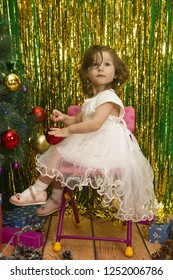 happy little girl in white dress decoration christmas tree  red balls