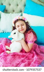 happy little girl with a white rabbit in bed at home