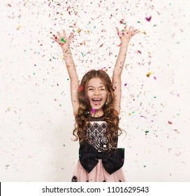 Happy little girl at white studio background, copy space. Portrait of beautiful spick and span child having fun with shiny confetti