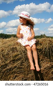 Happy little girl in white sundress and hat on the haystack