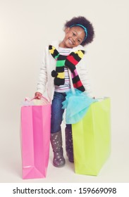 Happy little girl in winter attire with full shopping bags.