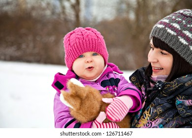 Happy little girl in winter with her mother