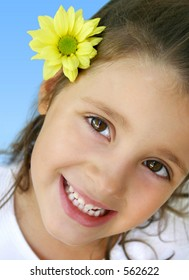 Happy little girl with an yellow daisy in her hair.