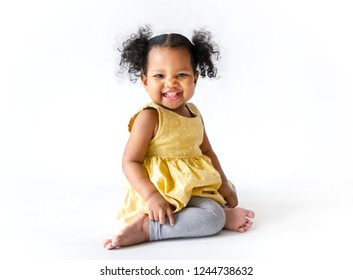 Happy little girl in a yellow dress sitting