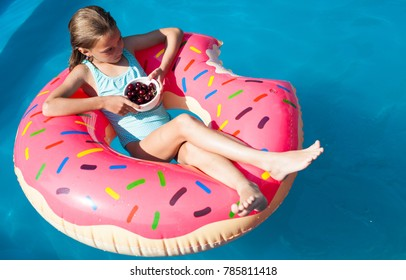 Happy little girleasting cherries on a colorful inflatable donut in a  swimming pool.