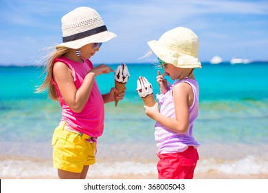 Happy little girls eating ice-cream over summer beach background. People, children, friends and friendship concept