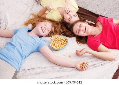 happy little girls  eating popcorn at home
