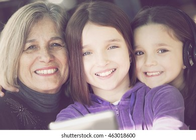 Happy little girls with grandmother having fun with mobile phone