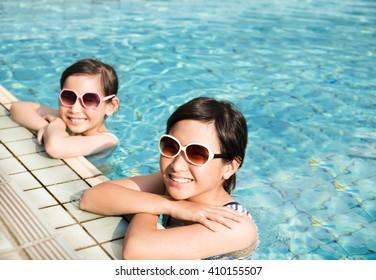 happy little girls having fun  in swimming pool