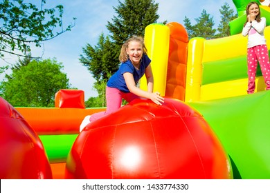 Happy little girls having lots of fun while jumping from ball to ball on an inflate house.