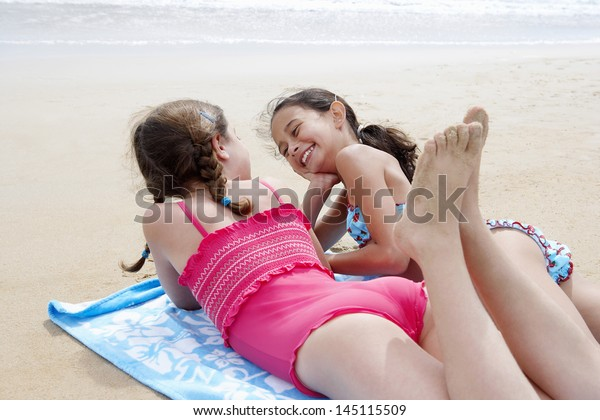 Cheerful little girl lying on her stomach on the wall