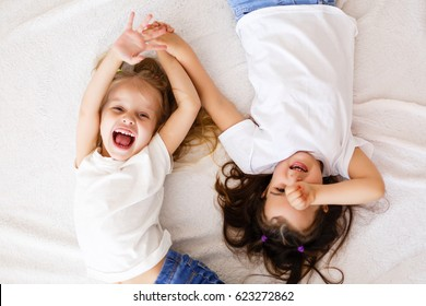 happy little girls lying on back top view sisters