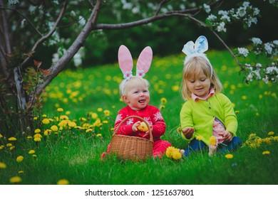 happy little girls on easter eggs hunt in spring
