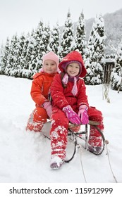 Happy little girls are on the sledge
