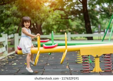 happy little girls on teetering board outdoor