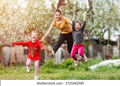 happy little girls sisters and twins jumping and playing in the garden with grass