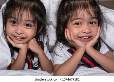 happy little girls twins sister in bed under the blanket having fun, smiling and wacky. Asian twins on bed white blanket happy and wacky