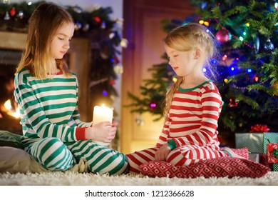 Happy little girls wearing Christmas pajamas playing by a fireplace in a cozy dark living room on Christmas eve. Celebrating Xmas at home.