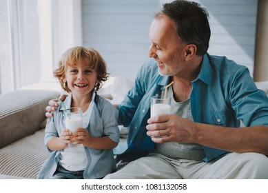 Happy little grandson drinks milk with straw in glass with grandfather. Use of calcium.
