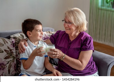 Happy little grandson drinks milk with straw in glass with grandmother. Use of calcium. Beautiful grandma with grandson drinking milk, healthcare concept.