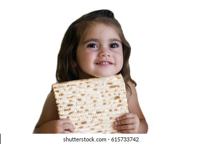 Happy little Jewish girl (age 03) holding a matzo on Passover Jewish holiday. Real people. copy space